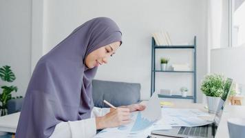 Beautiful Asia muslim lady in headscarf casual wear using laptop in living room at house. Remotely working from home, new normal lifestyle, social distancing, quarantine for corona virus prevention. photo