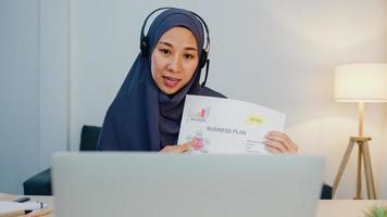 Asia muslim lady wear headphone using laptop talk to colleagues about sale report in conference video call while working from home office at night. Social distancing, quarantine for corona virus. photo