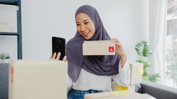 Young Asia muslim businesswoman blogger using mobile phone camera to recording vlog video live streaming review product at home office. Small business owner, start up online market delivery concept. photo