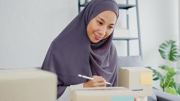 Young Asia muslim businesswoman check product purchase order on stock and save to tablet computer work at home office. Small business owner, online market delivery, lifestyle freelance concept. photo