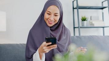 Asia muslim lady use smart phone, credit card buy and purchase e-commerce internet in living room at house. Stay at home, online shopping, self isolation, social distance, quarantine for coronavirus. photo