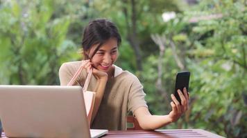 Mujer asiática que usa la publicación de selfie de teléfono móvil en las redes sociales, la mujer se relaja sintiéndose feliz mostrando bolsas de compras sentado en la mesa en el jardín por la mañana. las mujeres de estilo de vida se relajan en el concepto de hogar. foto