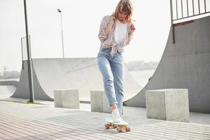 A young sports woman who rides in a park on a skateboard. photo