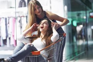 Young women have fun with the basket and listen to supermarket music in the evening photo