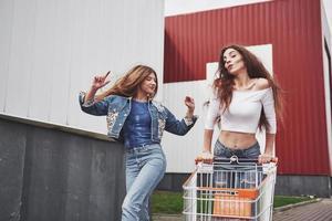 Two young happy women having fun shopping trolley race outdoors. photo