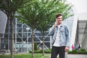 A handsome young man talking on the phone near the office space. photo