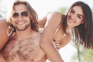 A los jóvenes hermosos les gusta. un hombre sostiene a una mujer sobre sus hombros, son juguetones y románticos foto
