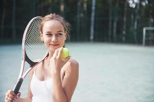 Cute girl playing tennis and posing for the camera. photo