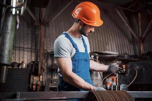 operador experimentado con casco. Concepto de la industria metalmecánica ingeniero profesional obrero metalúrgico operativo fresadora cnc centro en taller de fabricación foto