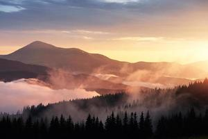 Beautiful sunset in the mountains. Landscape with sun light shining through orange clouds and fog photo