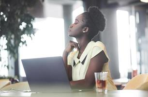 A young African American girl with dark curly hair pondering a laptop in a cafe photo