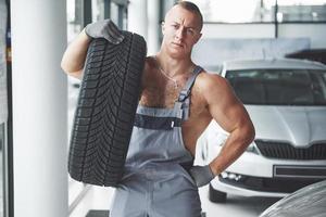 mecánico sosteniendo un neumático en el taller de reparación. sustitución de neumáticos de invierno y verano foto