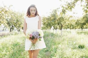 Hermosa joven vistiendo un elegante vestido blanco y disfrutando de una hermosa tarde soleada en un jardín de verano foto