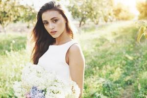 una hermosa joven con un vestido blanco claro y un ramo de flores de verano pone un buen día en el jardín foto