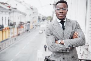 Confident black business man in a stylish suit standing on office block looking at the camera with a serious expression photo