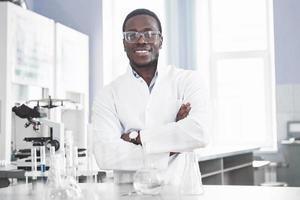el científico trabaja con un microscopio en un laboratorio realizando experimentos y fórmulas. foto