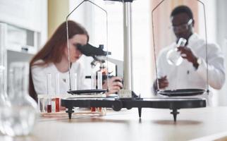 asistente de laboratorio con microscopio bombilla de cristalería de laboratorio con productos químicos. foto