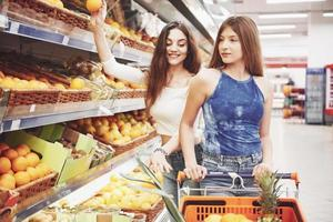 Two women choose seasonal fruits in the supermarket grocery store photo