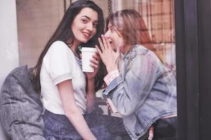 Two beautiful young women sitting in a cafe, drinking coffee and having a pleasant conversation after shopping photo