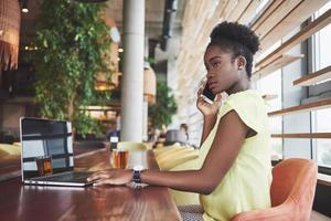 Joven y bella mujer de negocios afroamericana hablando por teléfono mientras trabajaba en un café foto