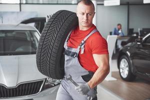 mecánico sosteniendo un neumático en el taller de reparación. sustitución de neumáticos de invierno y verano. foto