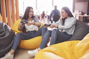 hermanas gemelas juegan en la consola. las niñas sostienen joysticks en sus manos y se divierten foto