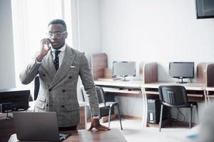 heerful african businessman standing in front of colleague photo