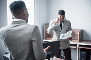 Modern businessman at work. Two confident business people in formalwear discussing something While one of them looks at the documents and the second an important phone call photo