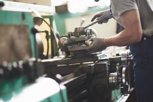manos fuertes sostienen la pieza de acero. en la antigua fábrica. foto
