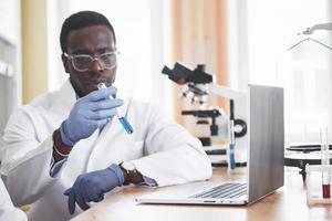 un trabajador afroamericano trabaja en un laboratorio realizando experimentos. foto