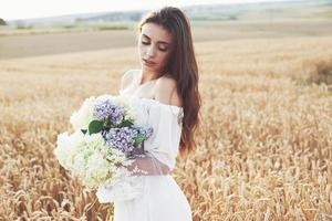 Beautiful girl in white dress running on the autumn field of wheat at sunset time photo