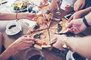 Dinner time. Close-up of tasty pizza on the table, with a lot of hands that take a piece photo