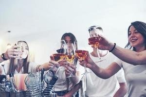 concepto de ocio y comunicación. Grupo de amigos sonrientes felices disfrutando de bebidas y hablando en el bar o pub foto