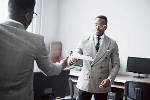 Discussing a project. Two black business people in formalwear discussing something while one of them pointing a paper photo