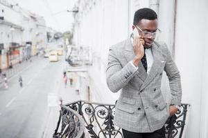 Young African man in formal wear talking on the mobile phone and smiling while standing outdoors photo