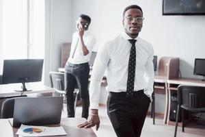 Working with smile. Heerful african businessman standing in front of colleague. photo