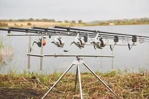 Carp fishing rods standing on special tripods. Expensive coils and a radio system of crochet photo
