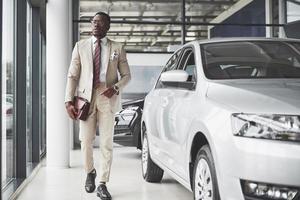 joven empresario negro en el fondo del salón del automóvil. concepto de venta y alquiler de coches foto