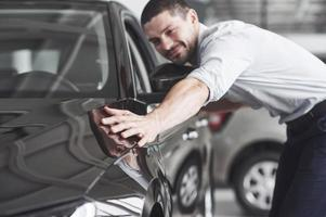 happy man touching car in auto show or salon. photo