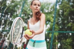 Portrait of a young tennis player standing ready for a serve. photo