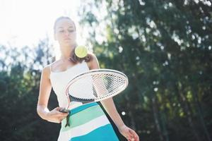 Woman in sportswear serves tennis ball. photo
