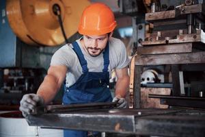 retrato de un joven trabajador con casco en una gran fábrica de reciclaje de residuos. el ingeniero supervisa el trabajo de las máquinas y otros equipos foto