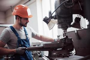 Experienced operator in a hard hat. Metalworking industry concept professional engineer metalworker operating CNC milling machine center in manufacturing workshop photo