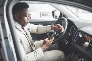 Stylish black businessman sitting behind the wheel of new luxury car. Rich african american man photo