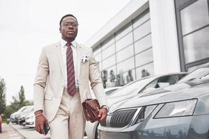 Visiting car dealership. Casual black business man in a suit near the car photo
