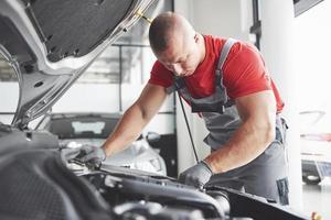 Imagen que muestra un trabajador de servicio de coche musculoso reparando el vehículo foto