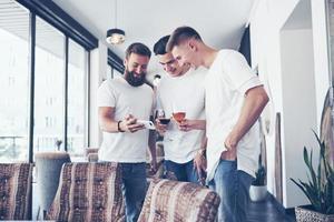 alegres viejos amigos se comunican entre sí y miran el teléfono, con vasos de whisky o vino en el pub. concepto de entretenimiento y estilo de vida. gente conectada wifi en reunión de mesa de bar foto