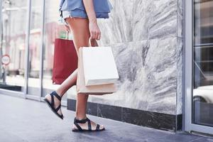 Closeup of woman holding shopping bags on the street in summer day photo