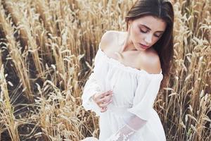 Sensible joven vestida de blanco posando en un campo de trigo dorado foto