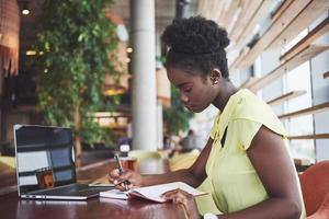 hermosa afroamericana trabajando en una computadora portátil en un restaurante. una mujer hermosa pensativa, todo en el trabajo. foto